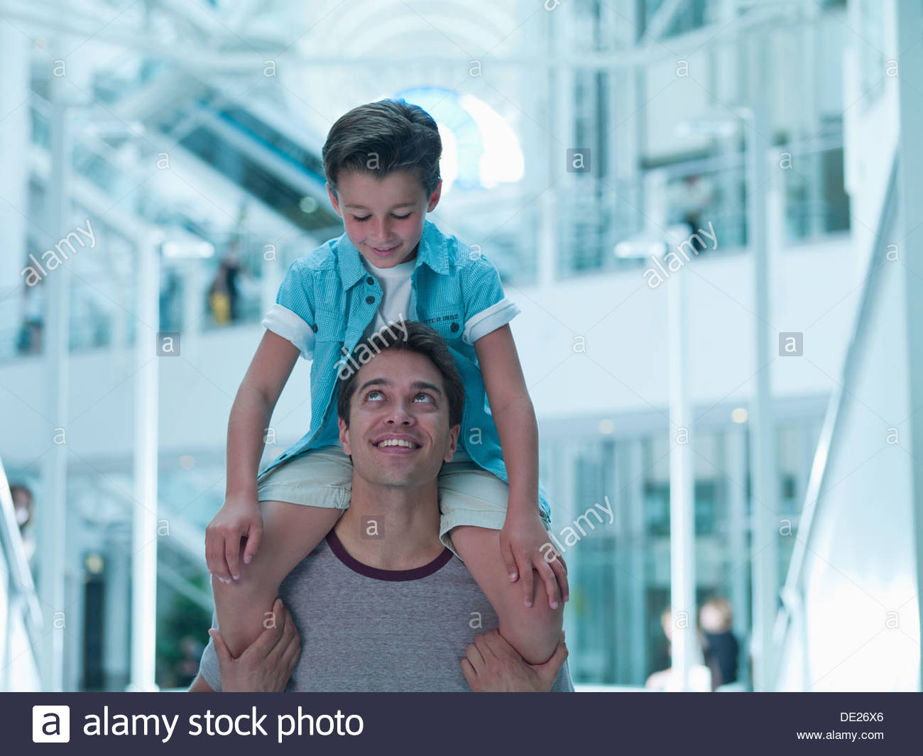 Father carrying son on shoulders in mall Photo Stock