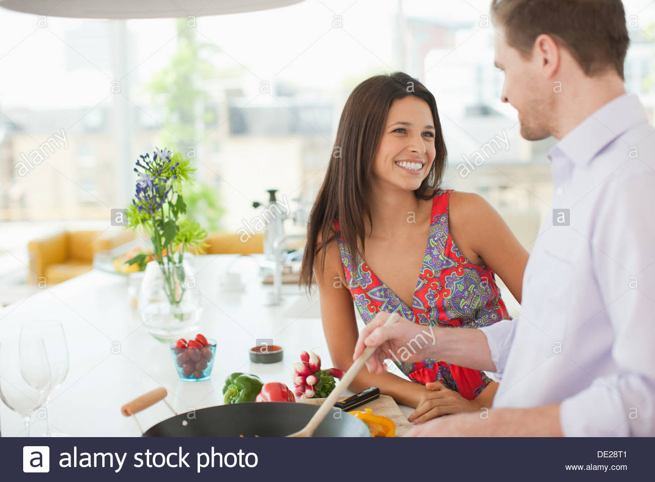 Femme regardant mari sauté au retournement dans la cuisine Photo Stock