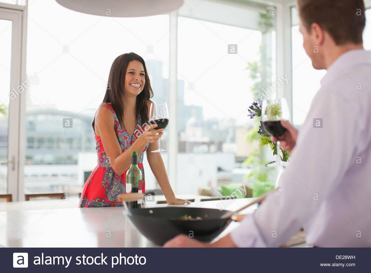Couple toasting en cuisine avec du vin rouge Photo Stock