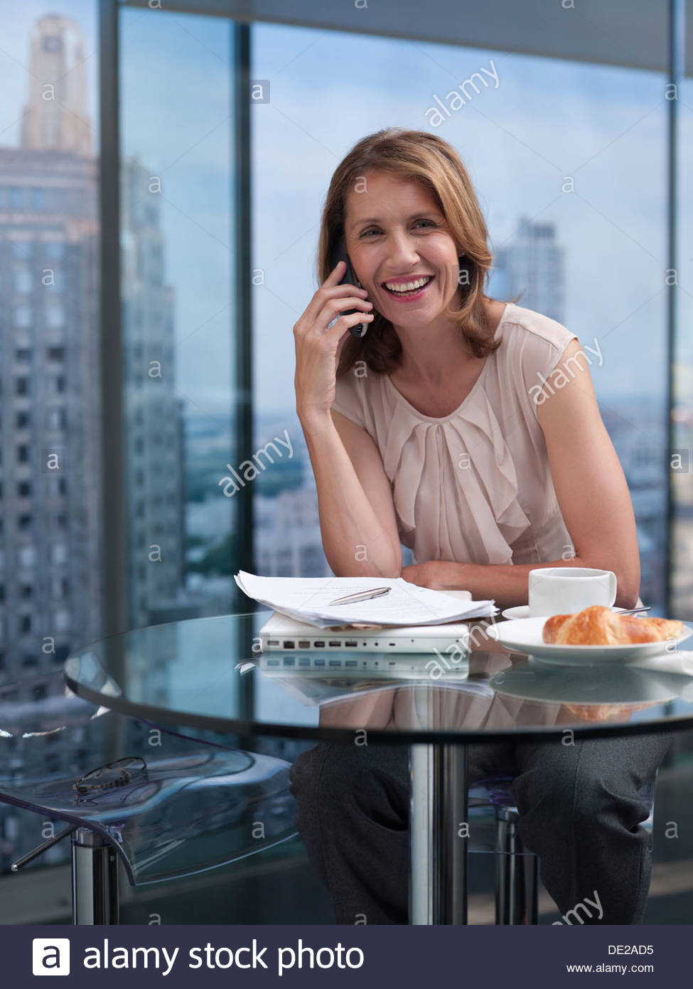 Femme parlant au téléphone avec cityscape in background Photo Stock