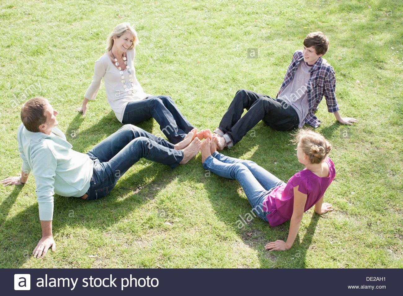 Family sitting on grass Photo Stock