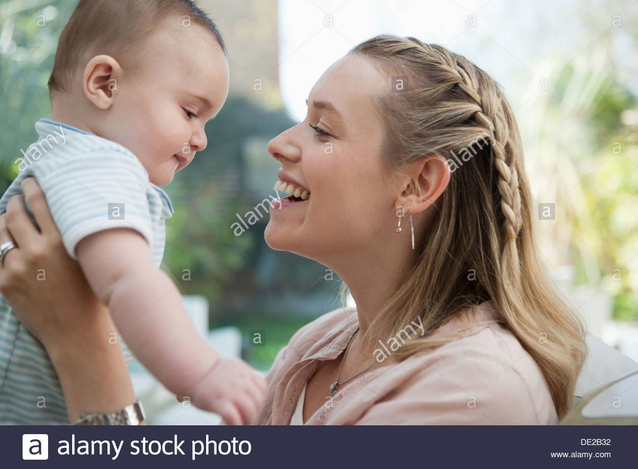 Smiling mother baby son anneau de levage Photo Stock