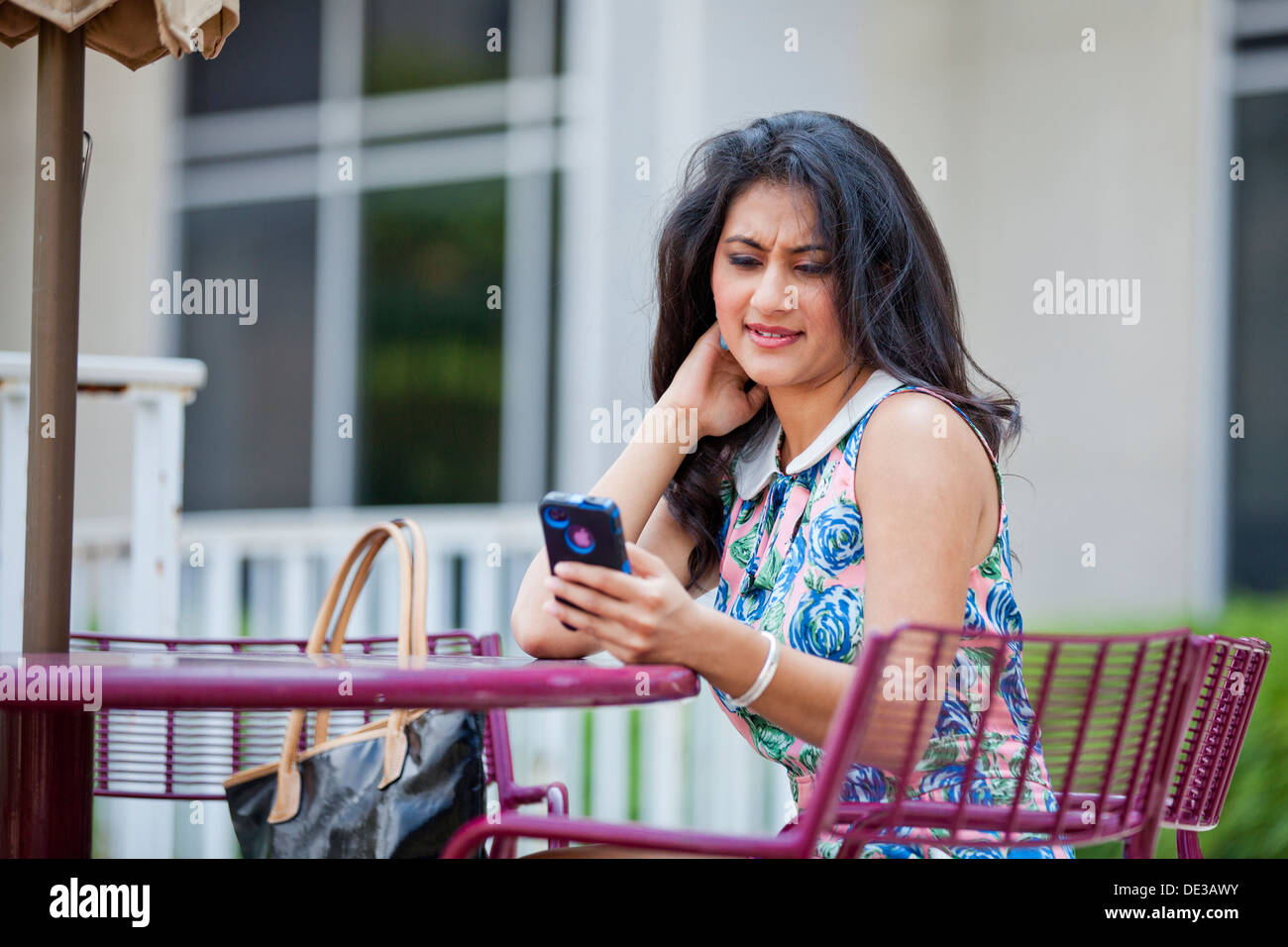 Concerné young woman looking at smart phone Photo Stock
