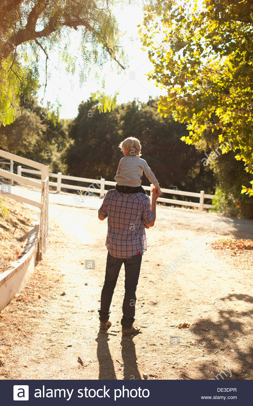 Father carrying son on shoulders Photo Stock