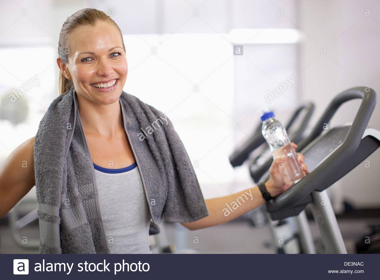 Femme avec de l'eau en bouteille dans la salle de sport Photo Stock
