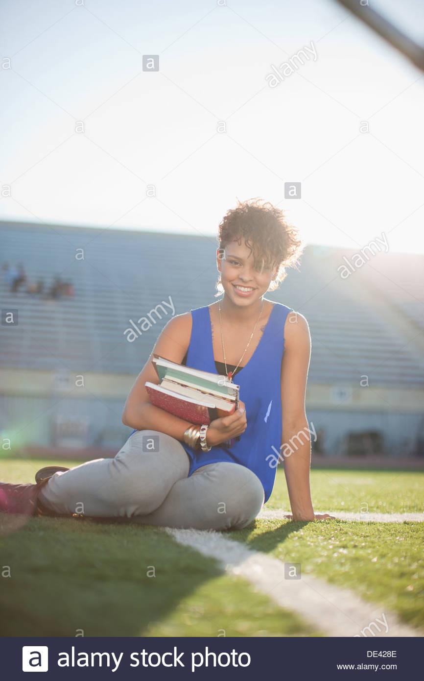 Student portant des livres sur terrain de football Photo Stock