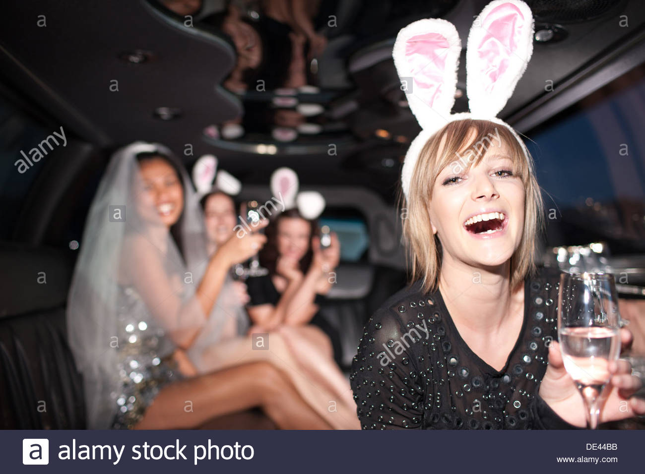 Woman in Bunny Ears drinking champagne in limo Photo Stock