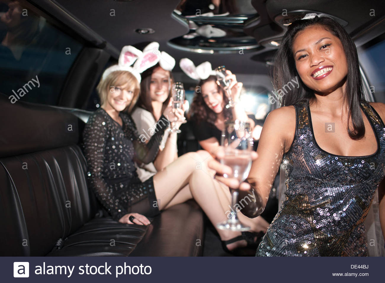 Woman drinking champagne in limo Photo Stock