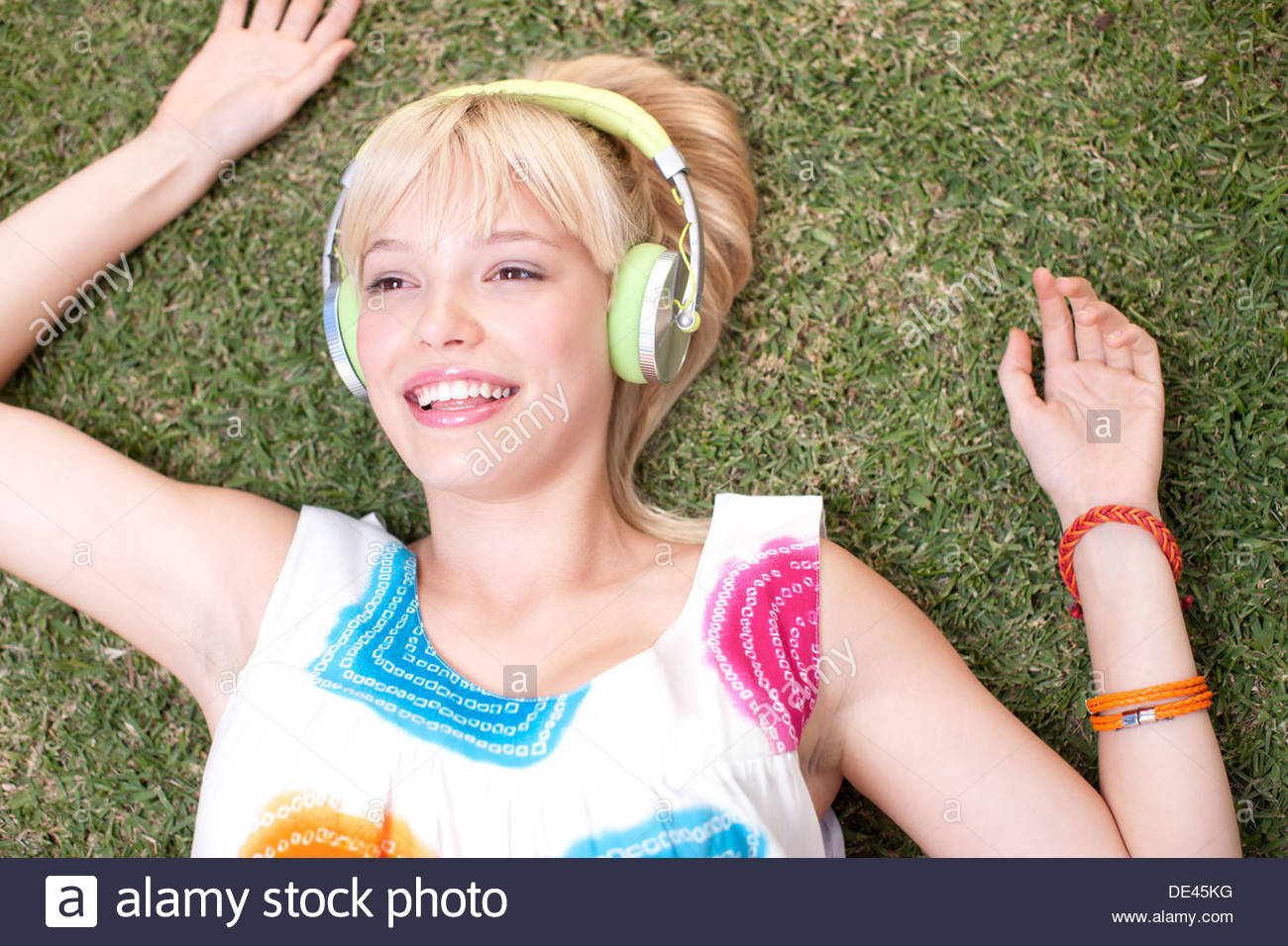 Woman laying on grass listening to headphones Photo Stock