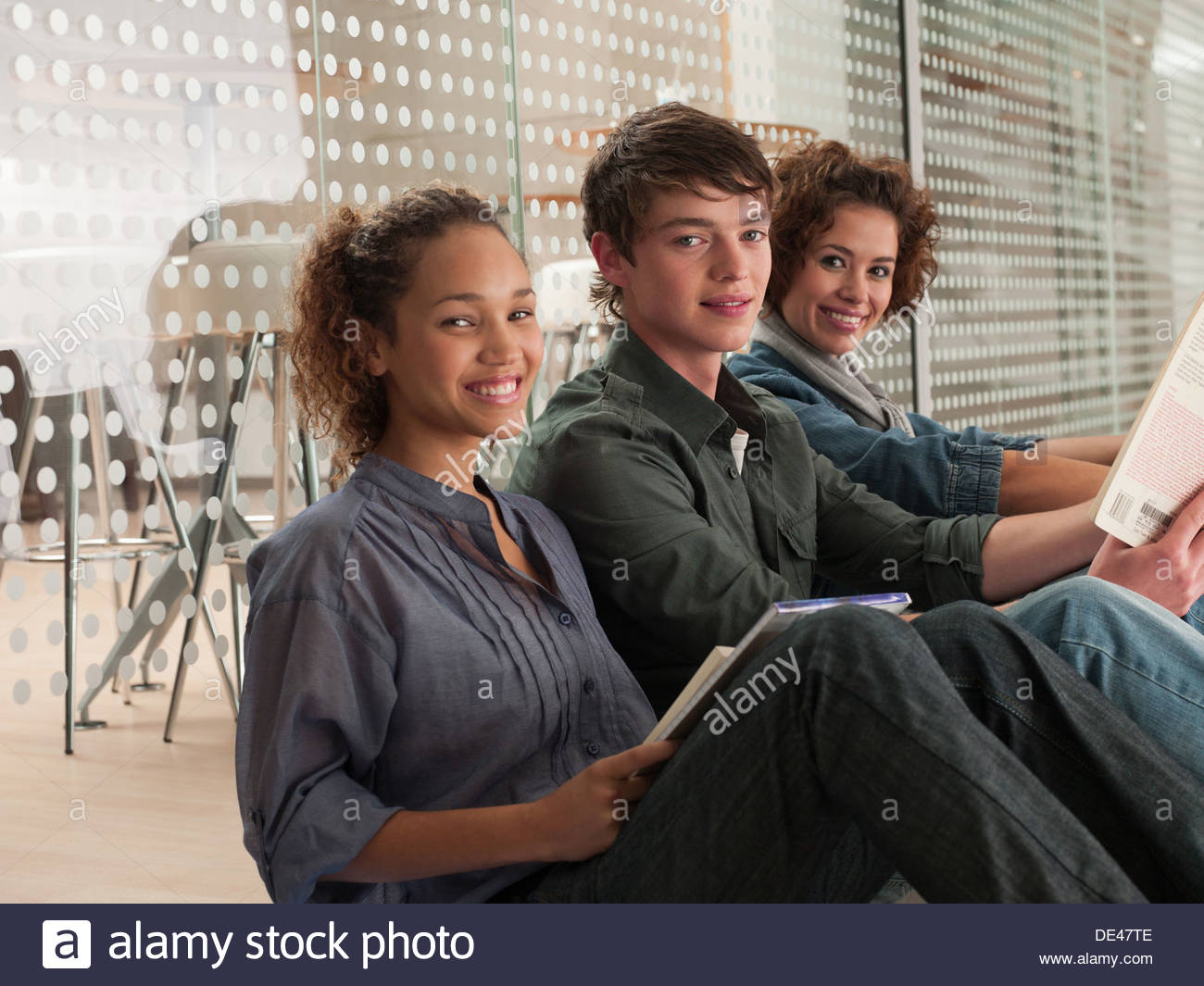 Smiling friends sitting in a row with holding book Photo Stock