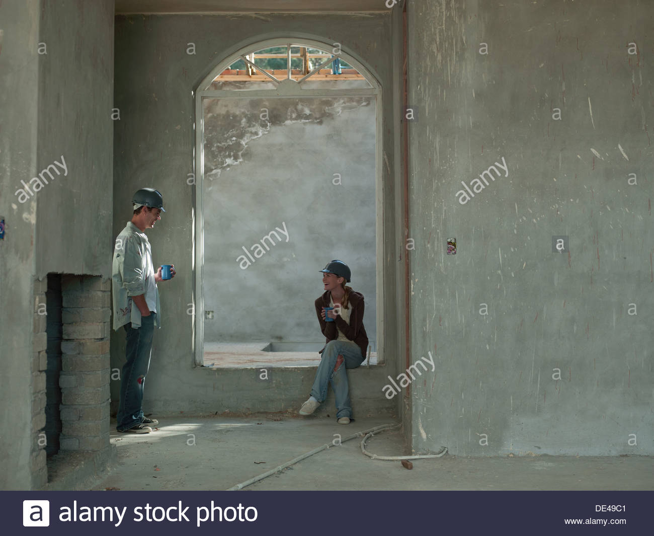 Couple drinking coffee in house under construction Photo Stock
