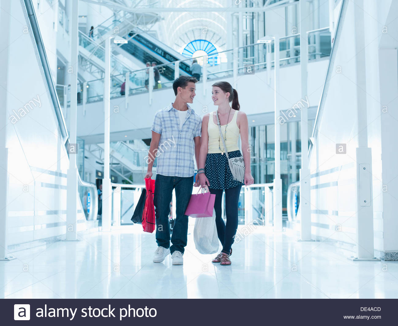 Smiling couple carrying shopping bags in mall Photo Stock