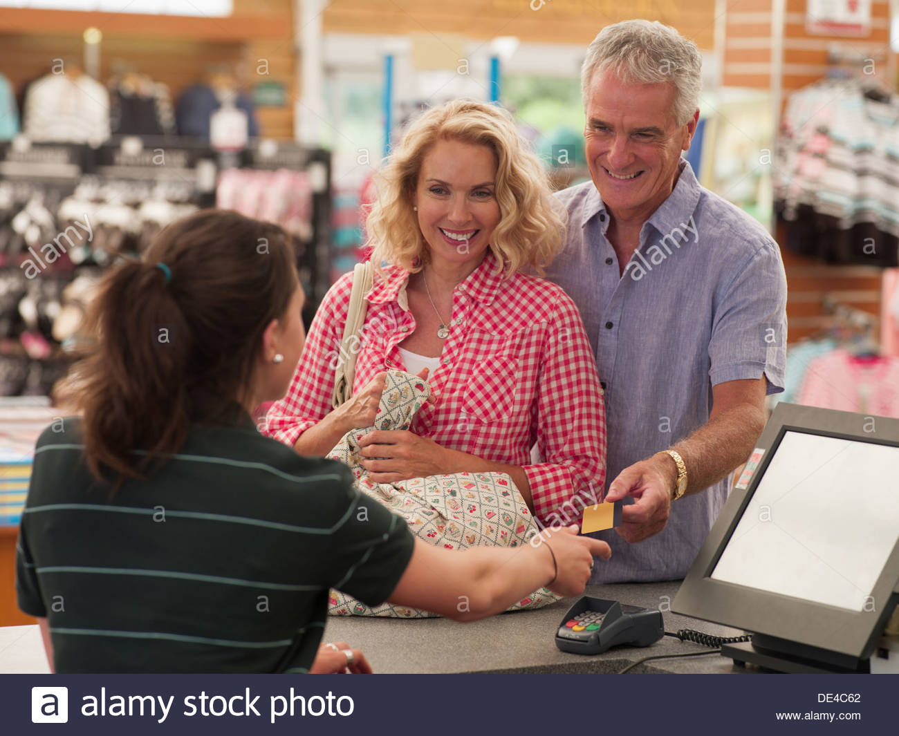 Achats du couple numérisation caissier dans le magasin Photo Stock