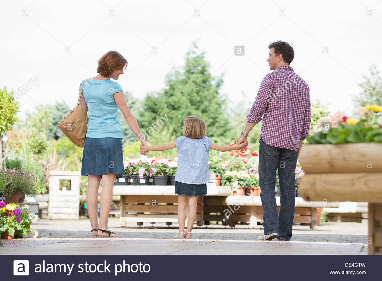 Les parents holding hand fille en maternelle Photo Stock