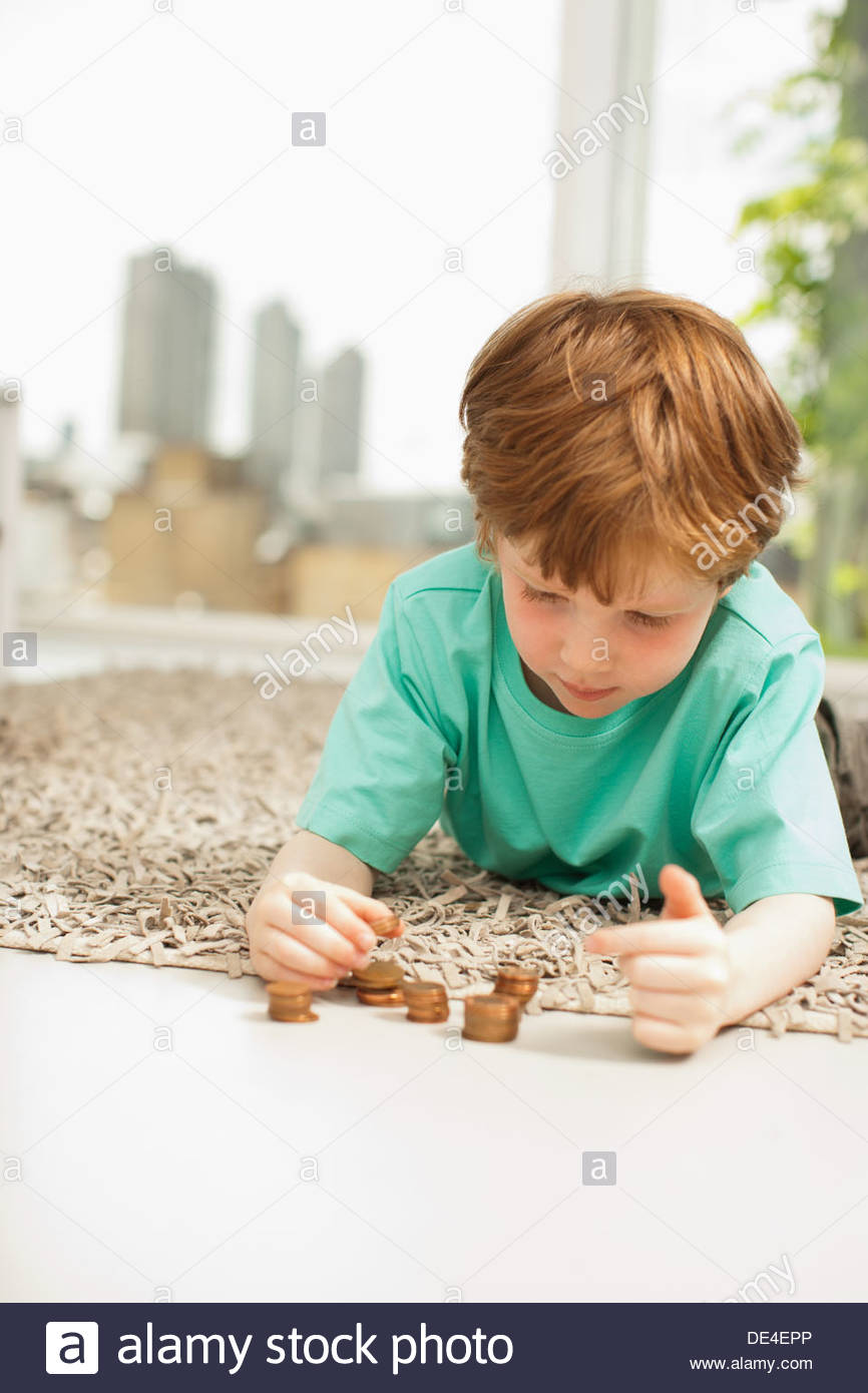 Serious boy stacking pennies sur marbre Photo Stock