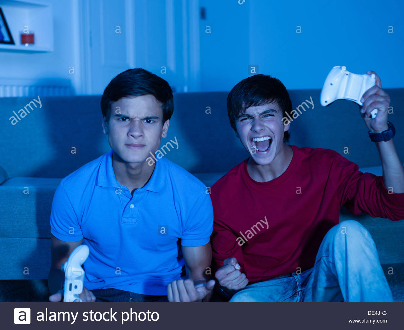 Smiling teenage boys playing video game Photo Stock
