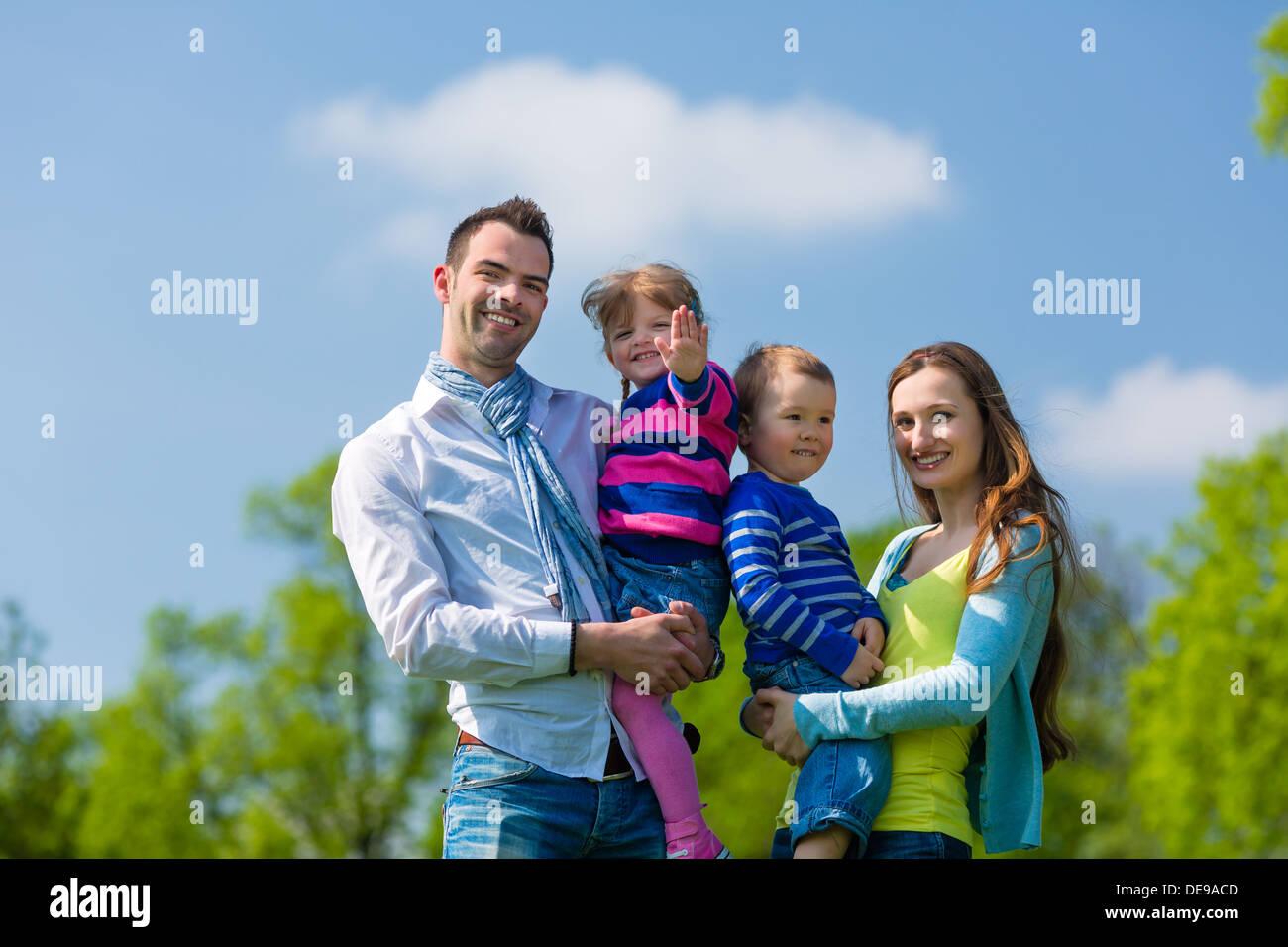 Famille heureuse avec sa fille et son fils marchant sur une prairie en été Banque D'Images