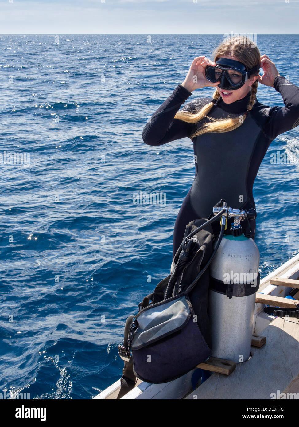 Caucasian woman sur un bateau dans l'océan d'ajuster ses lunettes en préparation pour la plongée. Photo Stock