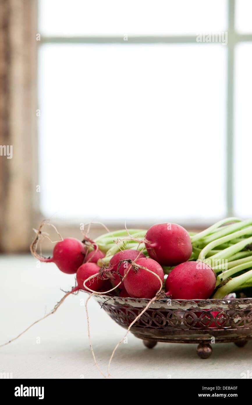 Un bol plein de radis frais contre une fenêtre illuminée. Photo Stock