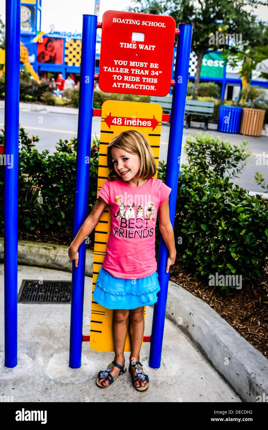 Jeune fille se tient devant le restricteur de hauteur à thème Legoland Florida Photo Stock
