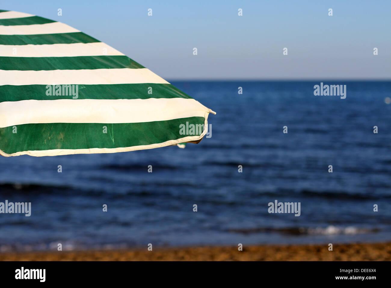 Parapluie vert et blanc sur la plage sans que personne au coucher du soleil en vacances Photo Stock