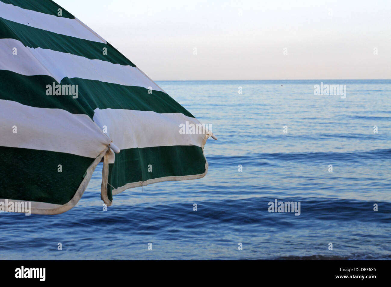 Vert et blanc parasol à la plage sans que personne au coucher du soleil en vacances Photo Stock