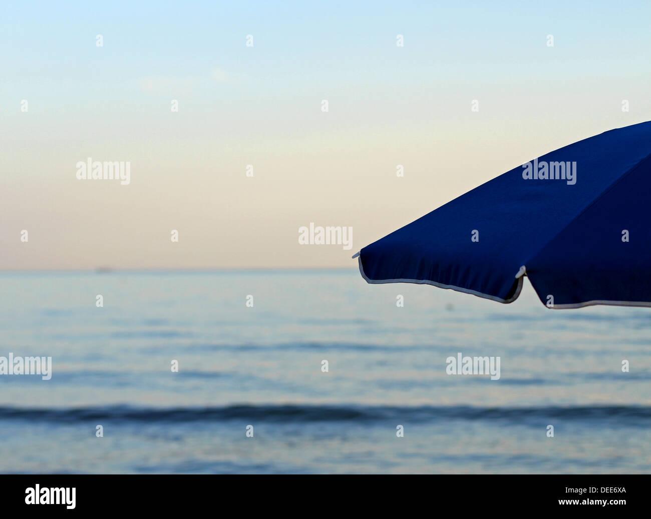 Parapluie bleu à la plage sans que personne au coucher du soleil en vacances Photo Stock