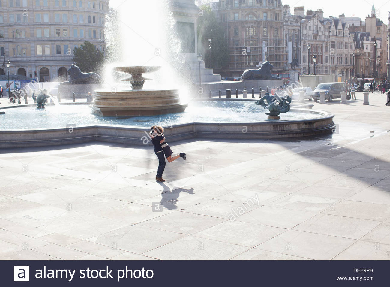Man lifting woman in front of urban fountain Photo Stock