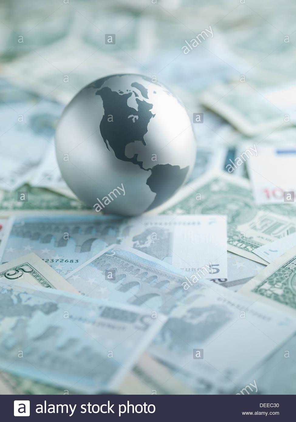 Metal globe posé sur du papier-monnaie Photo Stock