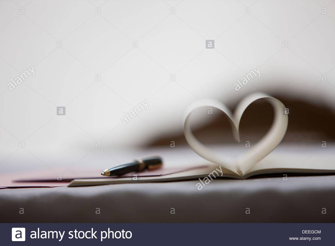 Stylo et bloc-notes de pages en forme de coeur de formage Photo Stock