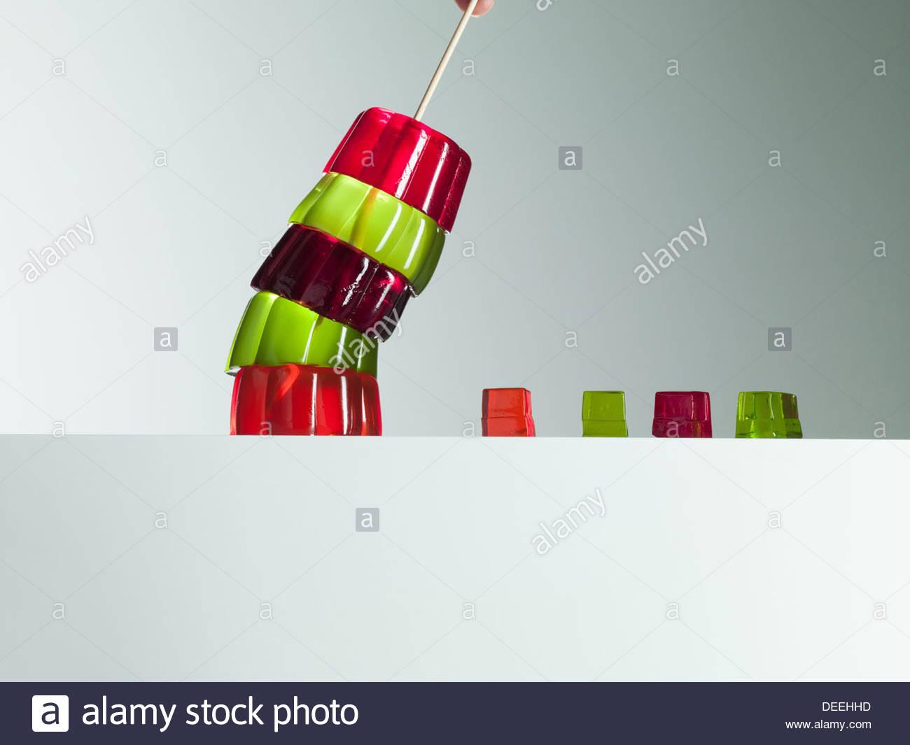 Pile de gélatine dynamique dessert penché au-dessus de petits cubes de gélatine dessert Photo Stock