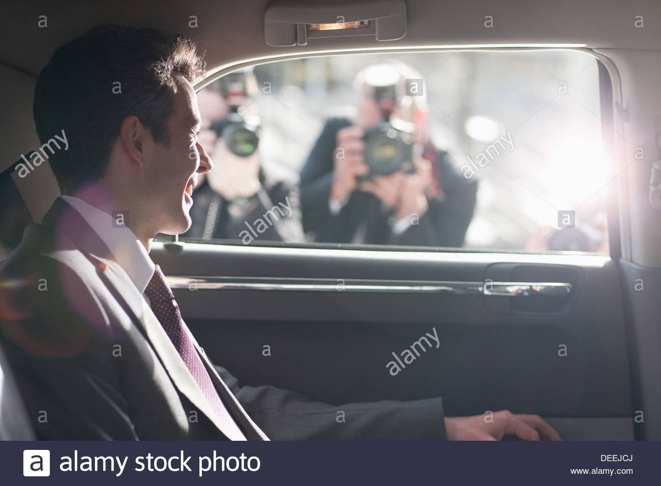 Smiling politicien pour paparazzi in backseat of car Photo Stock