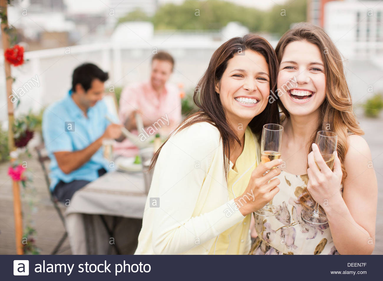 Laughing friends drinking Champagne at outdoor party Photo Stock
