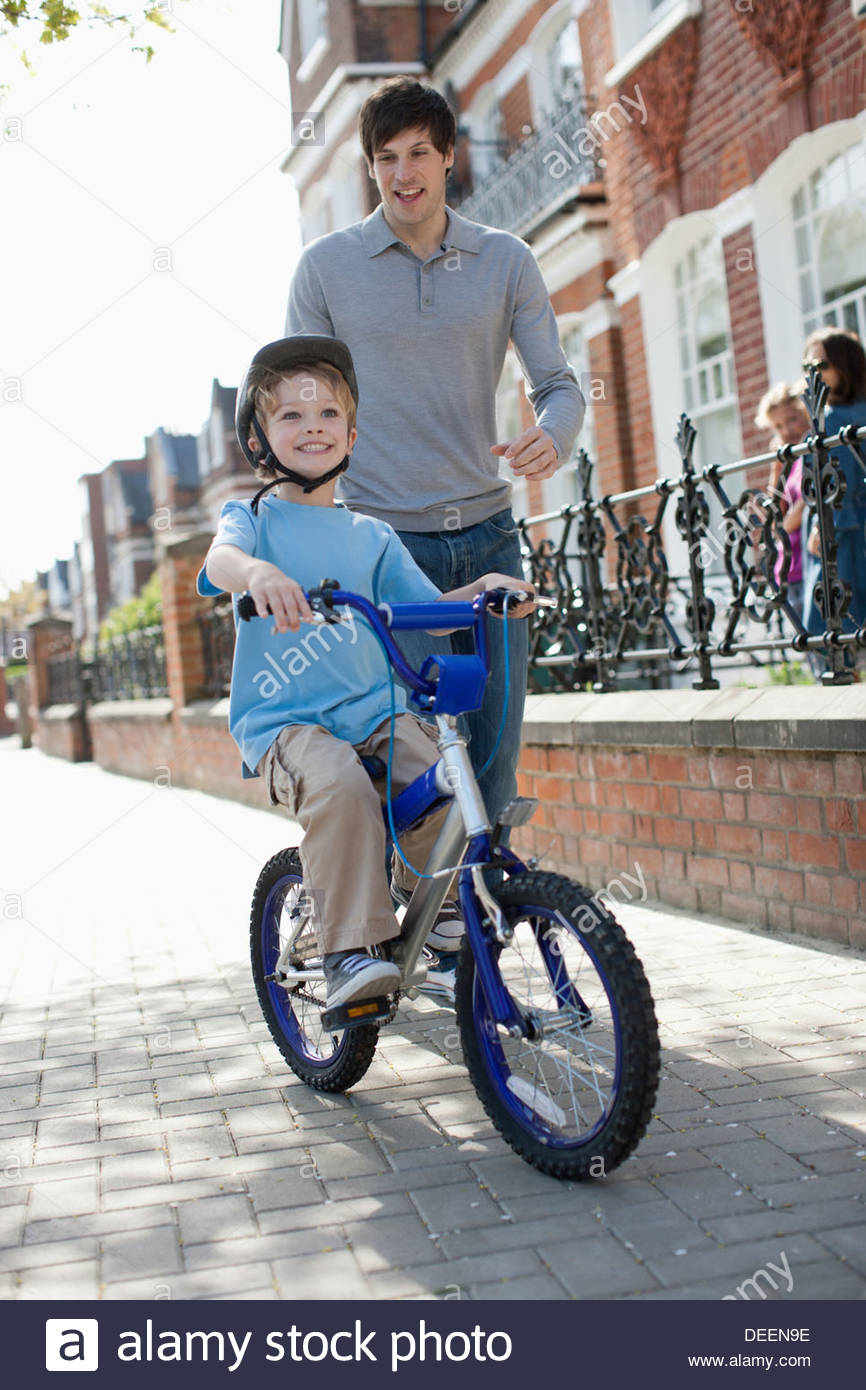 Père Fils regarder circuler à bicyclette sur le trottoir Photo Stock