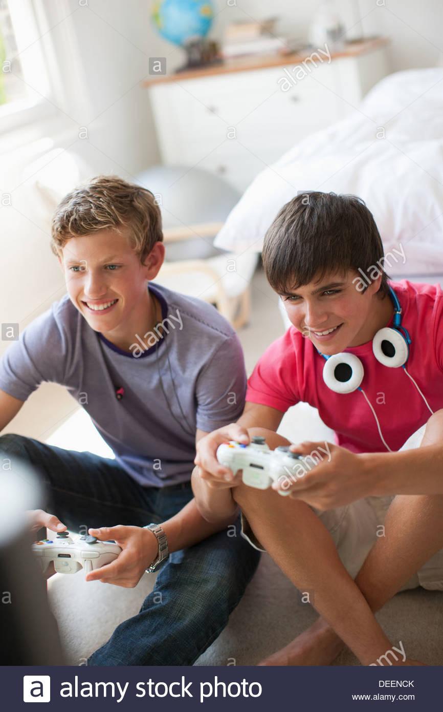 Smiling teenage boys playing video game Photo Stock