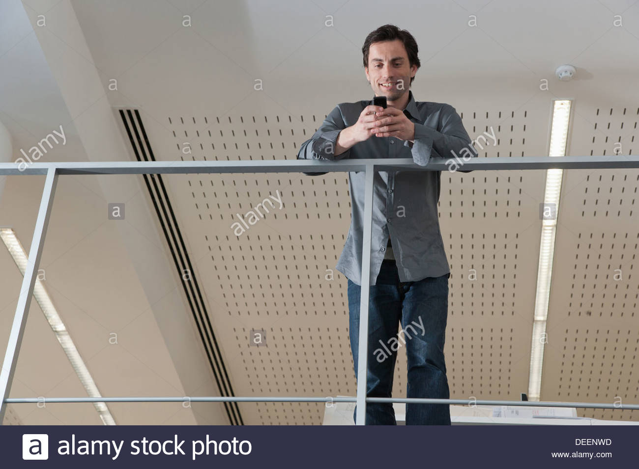 Businessman leaning on rail avec using cell phone in office Photo Stock