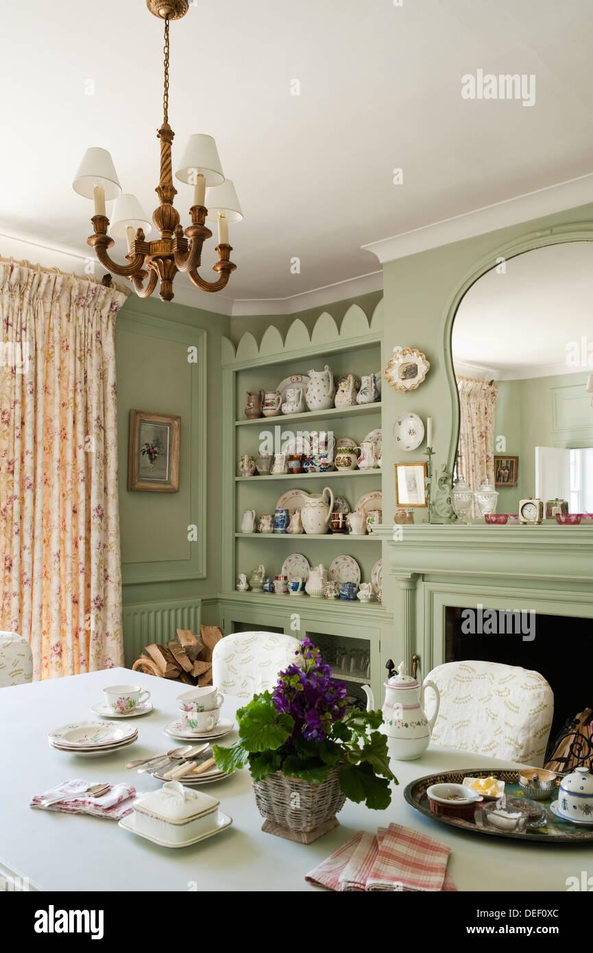 Country house salle à manger avec pottert collection sur des étagères encastrées peint en vert pastel Photo Stock