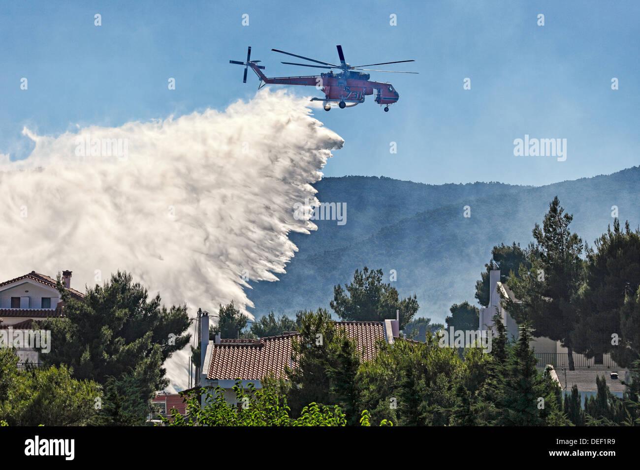Un hélicoptère de lutte contre l'incendie éteint l'incendie plus de maisons Photo Stock