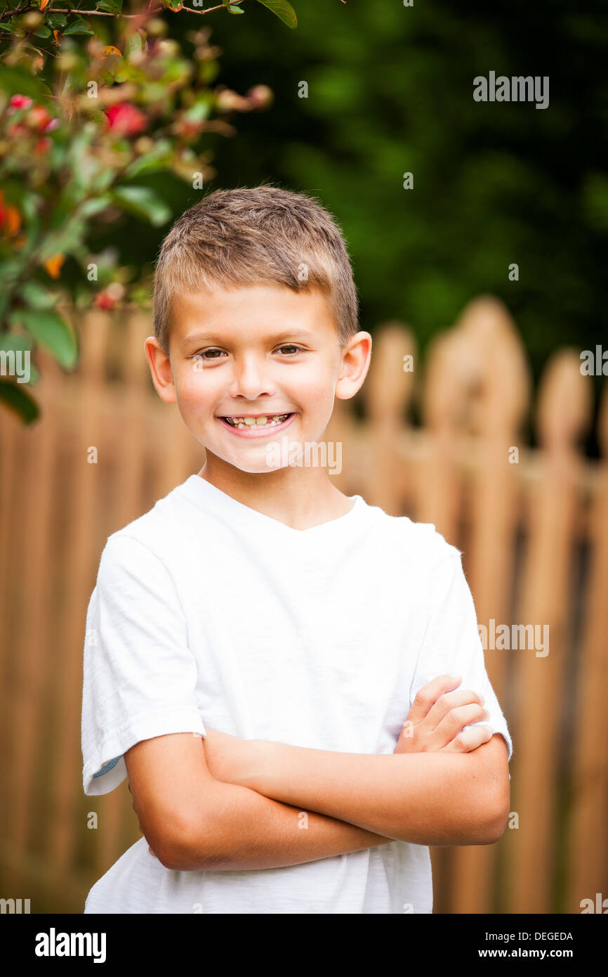 Boy crossing arms and smiling Photo Stock