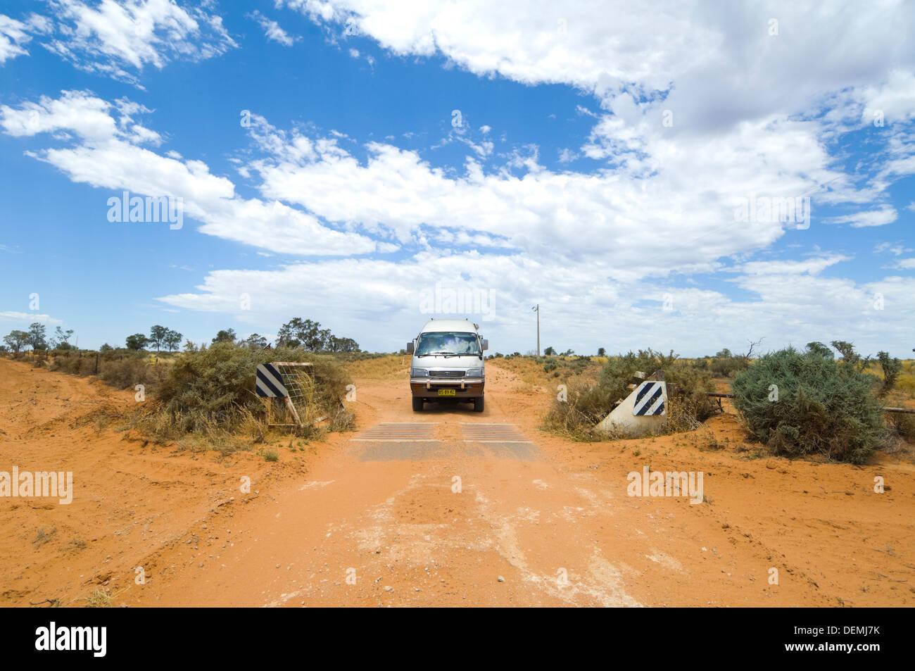 Aller sur une grille de bétail sur un chemin de terre dans une Toyota Hiace campervan, Mungo National Park, New South Wales, Australie Banque D'Images