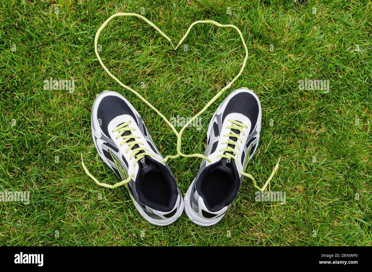 Baskets blanches pour courir sur l'herbe avec coeur Photo Stock