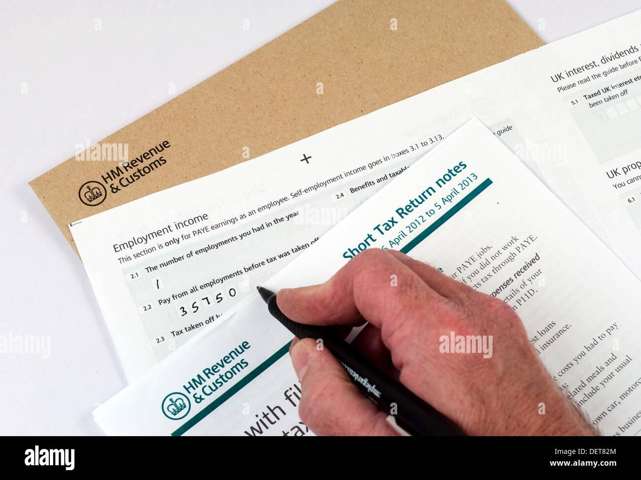 Personne remplissant les formulaires de déclaration de revenus Photo Stock
