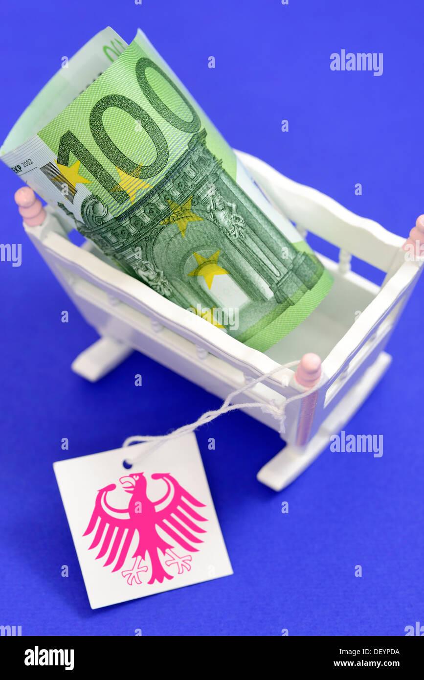 Berceau de l'enfant avec des centaines d'euro et de l'étiquette avec l'aigle fédéral, photo symbolique de l'argent, Kinderwiege soins mit Hundert-Euro-Schei Photo Stock