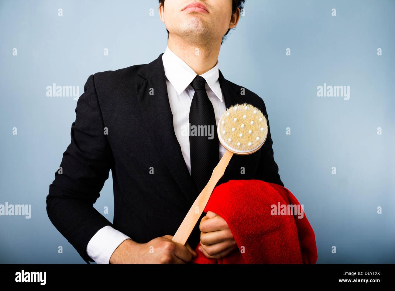 Jeune homme avec une serviette rouge brosse douche Photo Stock