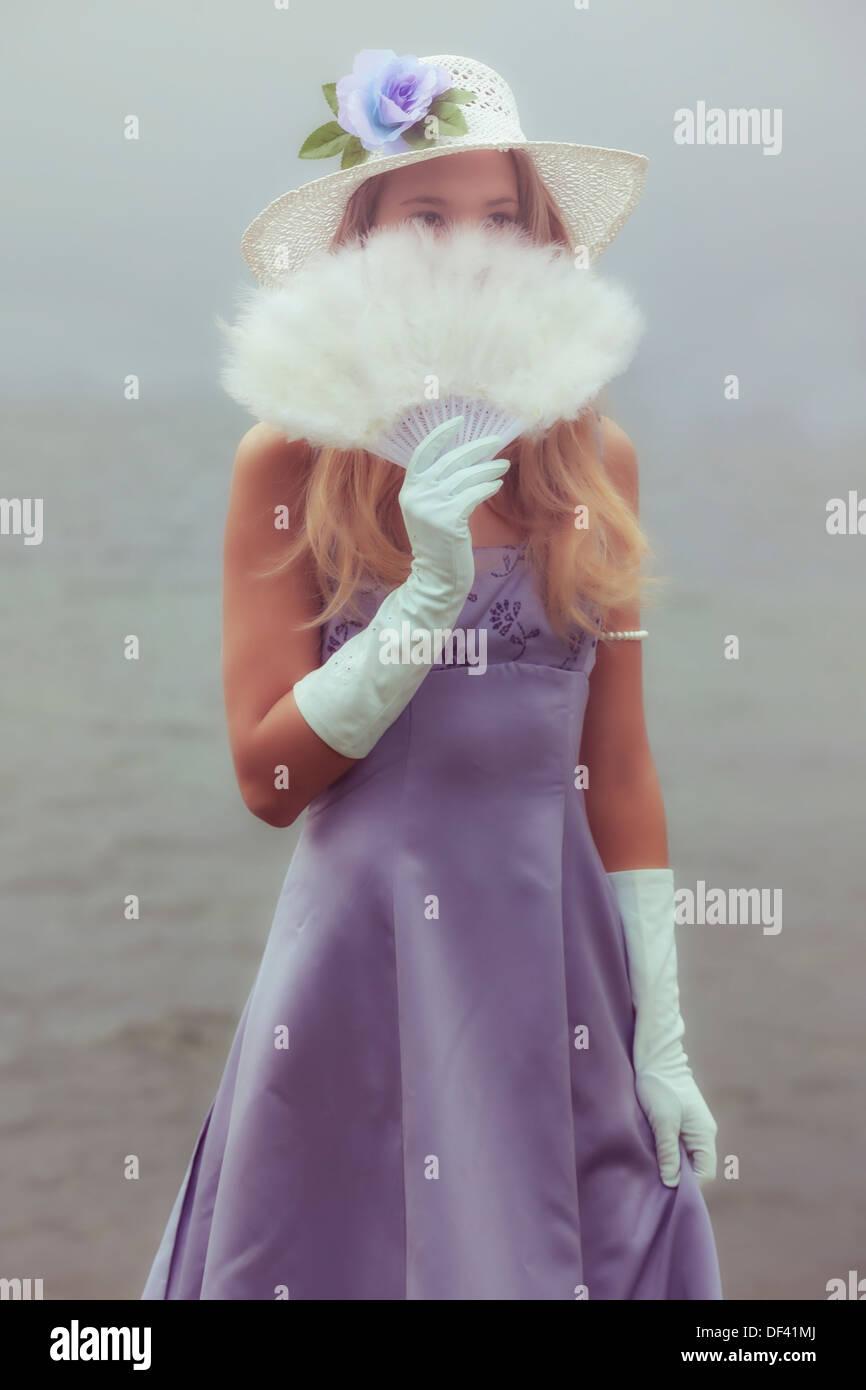 Une fille avec un chapeau de soleil se cache derrière une plume blanche ventilateur Photo Stock
