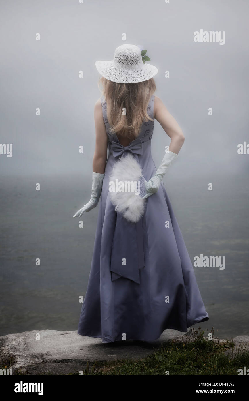 Une fille dans une robe pourpre avec chapeau de soleil et un ventilateur est debout à un lac Photo Stock