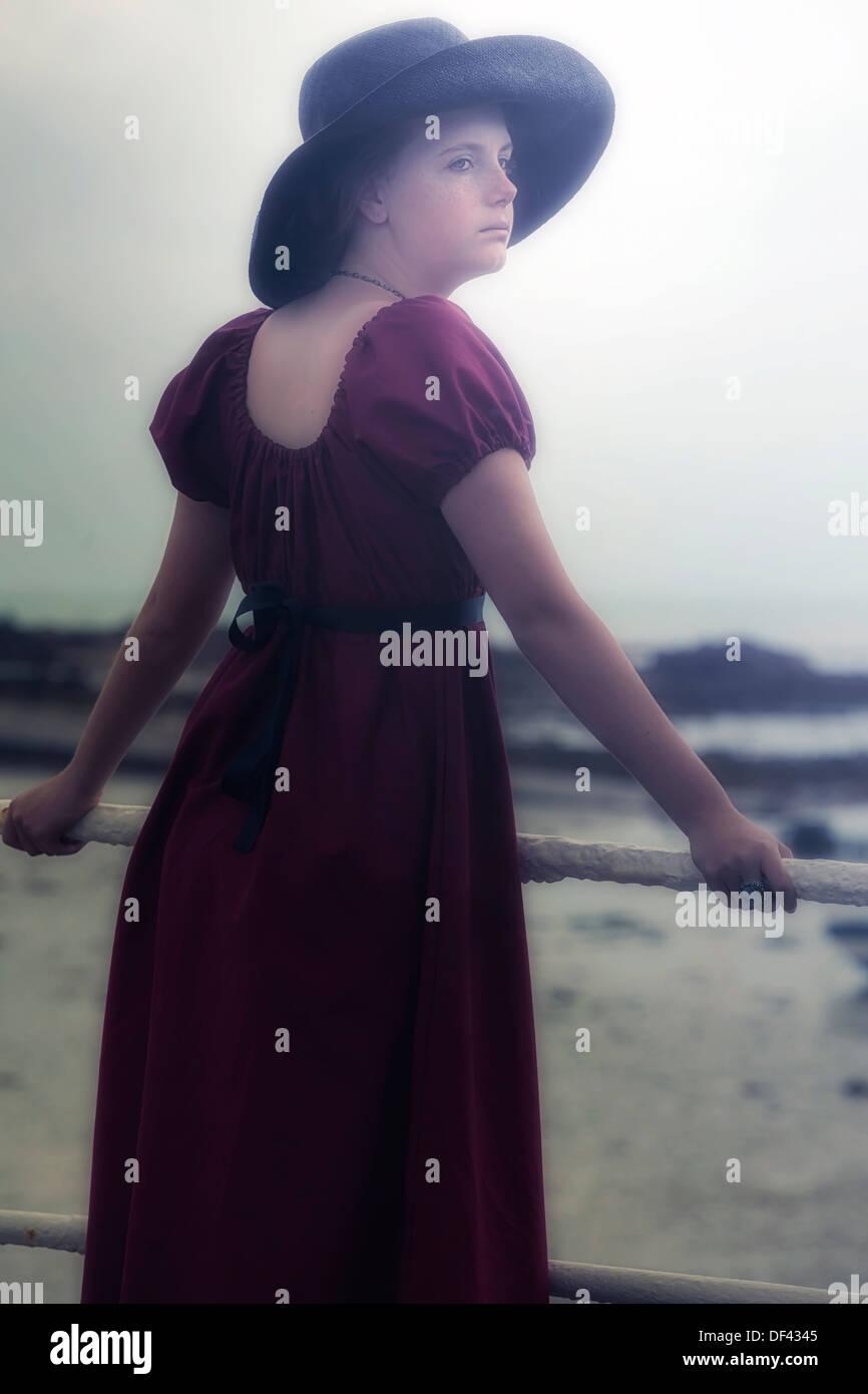 Une jeune fille dans une robe rouge est debout à une rampe en blanc à la mer Photo Stock