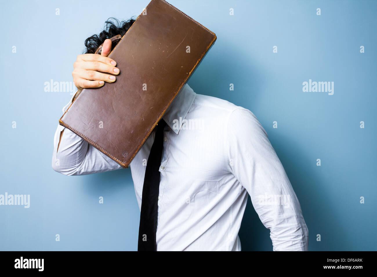 Jeune homme se cache son visage derrière un porte-documents Photo Stock
