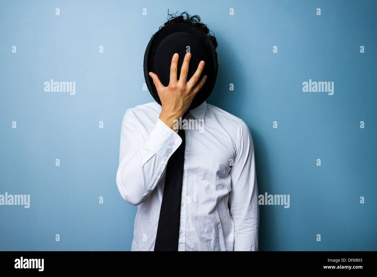 Jeune homme cachant son visage derrière son chapeau melon Photo Stock