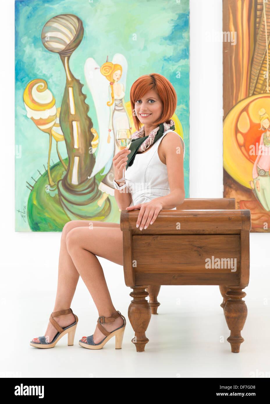 Les femmes attirantes jeunes assis sur un banc en bois, tenant un verre de vin et souriant, avec des peintures colorées sur l'arrière-plan Banque D'Images